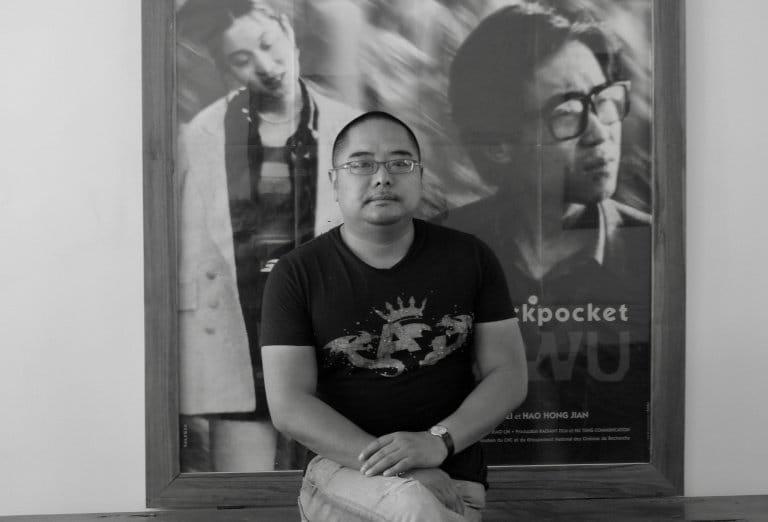 海波,诗人,坐在贾樟柯签名海报《小武》前,大理,2010